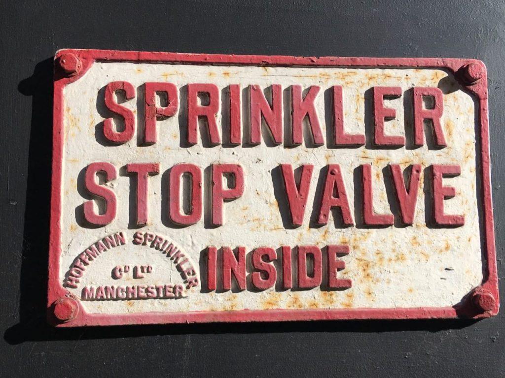 "Photo of a sign that says, ""Sprinkler shut-off valve inside"""